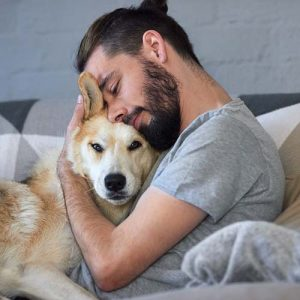 A dog sitter hugs the dog he's caring for